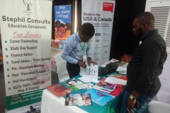 Mr. Olamide arranging Stephil Consults' souvenir for an enquirer at an exhibition